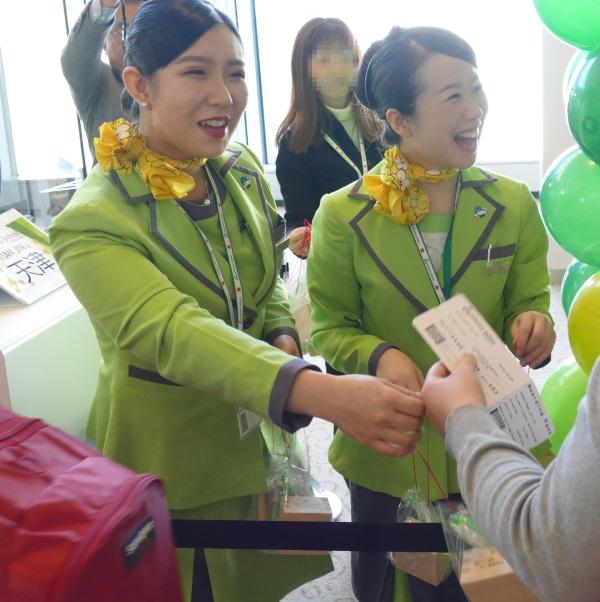 天津行きの初便の乗客に記念品を配る春秋航空日本の客室乗務員