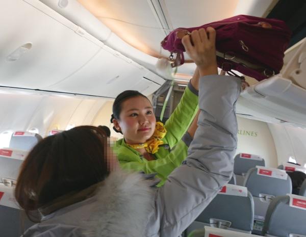 乗客の手荷物の上げ下げも手伝う春秋航空日本の客室乗務員