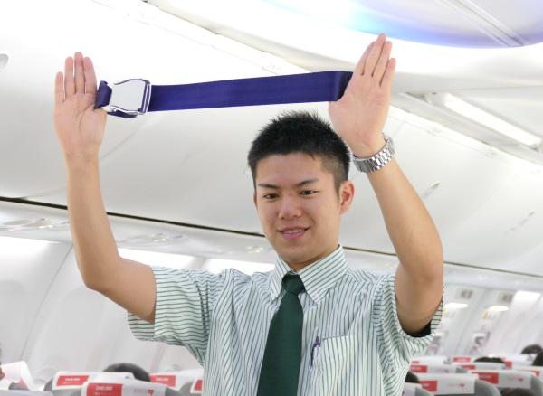 出発前に機内の安全設備のデモンストレーションを行う春秋航空日本の男性客室乗務員