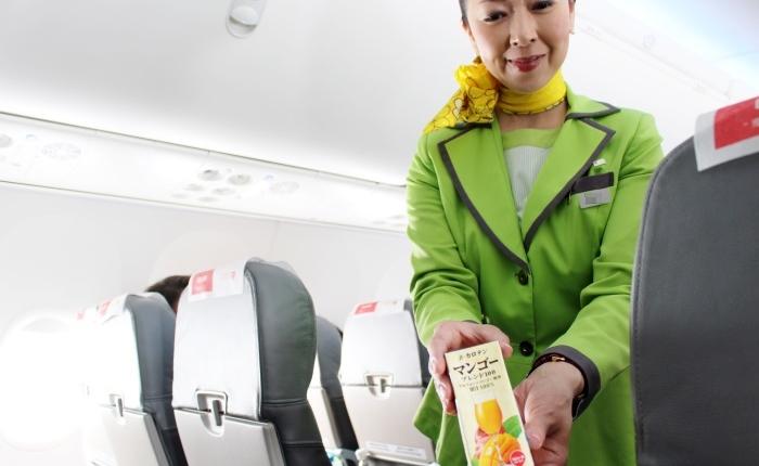 成田から広島に向かうLCC春秋航空日本(Spring Japan)で丁寧な接客を行う客室乗務員