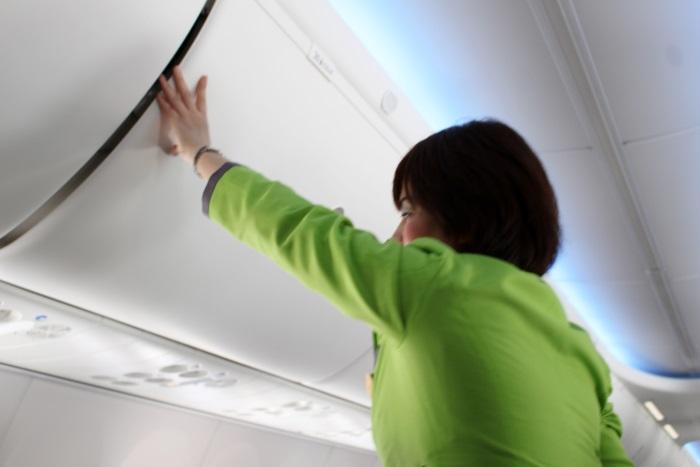 荷物棚が完全に締まっているかを何度も手で触れて確認する客室乗務員