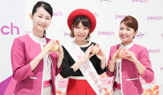 関西空港で行われたLCCピーチ・アビエーションの「和歌山桃キャンペーン」で配布した「紀の川市(JA紀の里)の桃」を持つ客室乗務員とー「紀の川ぷるぷる娘」