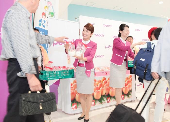 「和歌山桃キャンペーン」で搭乗客に桃を配るピーチ・アビエーションの客室乗務員
