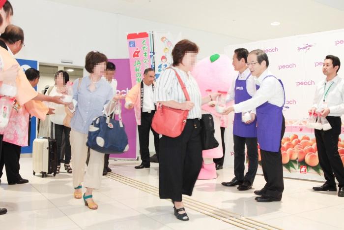 和歌山出身の金澤栄次監査役(写真右端)と井上慎一CEOも桃を配布