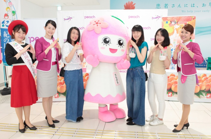 紀の川市のフルーツキャラクター「ももぷる」(写真中央)と桃を受け取った搭乗客ら