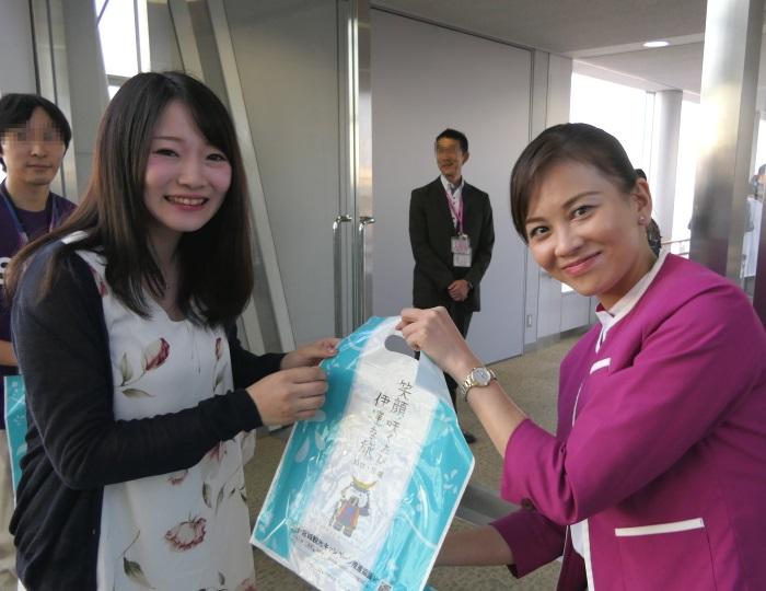 現役のCAさん自らが初便搭乗記念品を手渡し
