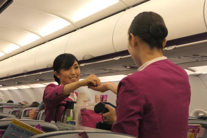 笑顔でコミュケーションしながら機内販売を行う