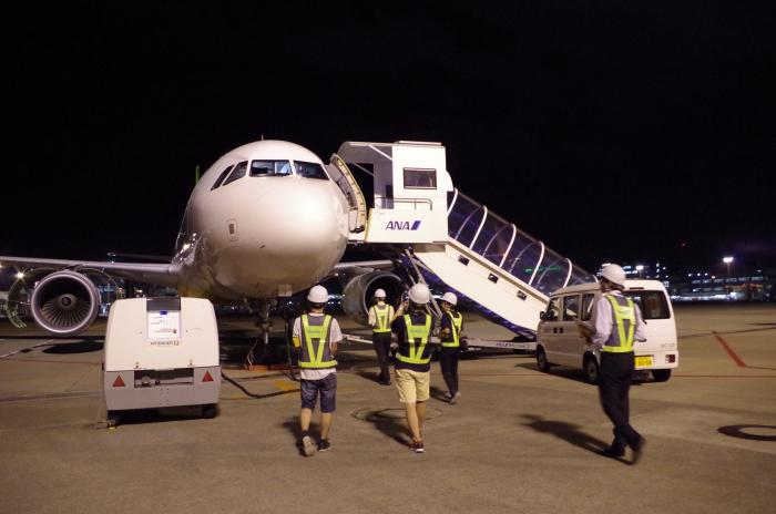 整備中の機体「JA11VA」にむかうメンバー
