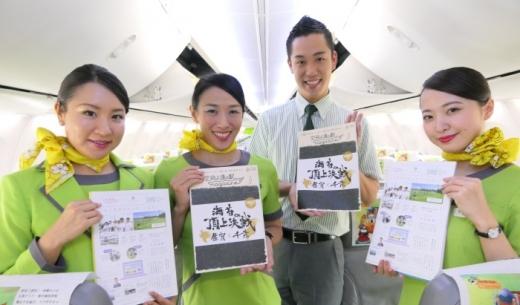春秋航空日本の機内誌「空飛ぶ道の駅 magazine」の最新号(vol.12)を持つ客室乗務員