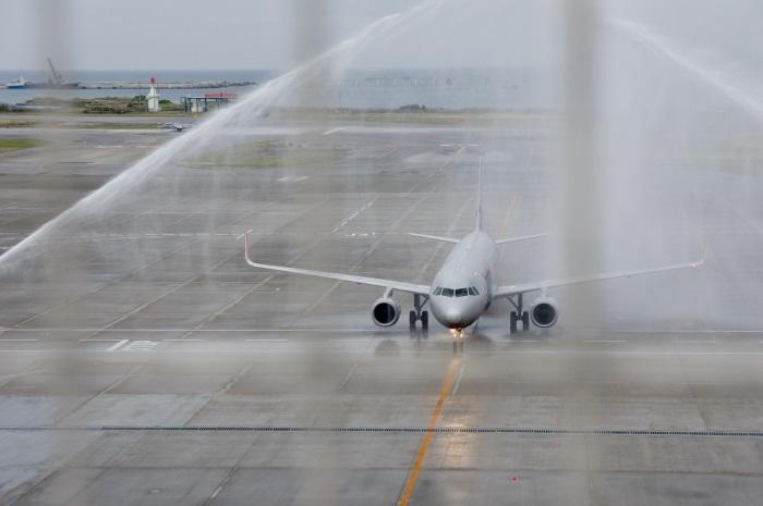 那覇空港に到着し、ウォーターキャノンで祝福されるジェットスター・アジア航空のシンガポール発3K791便